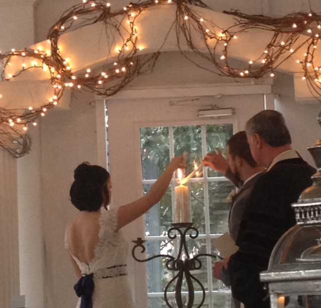 Flint Hill Wedding in historic Norcross near Atlanta lighting unity candle wearing lace wedding gown with sash
