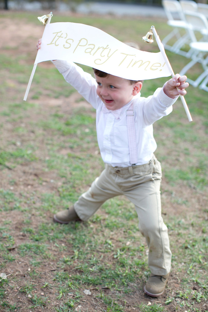 Ring bearer holding Its party time sign before wedding reception at Callanwolde fine arts center in Atlanta