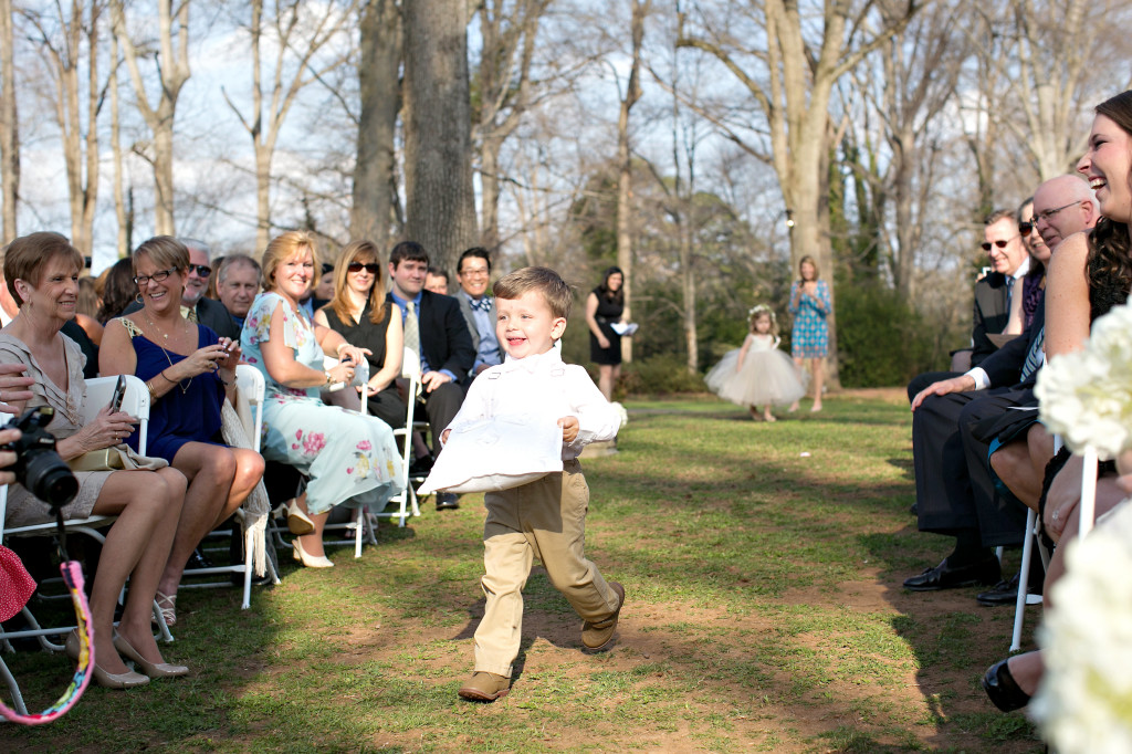 Ring bearer happily running down the aisle at outdoor Atlanta wedding callanwolde gardens fine arts center