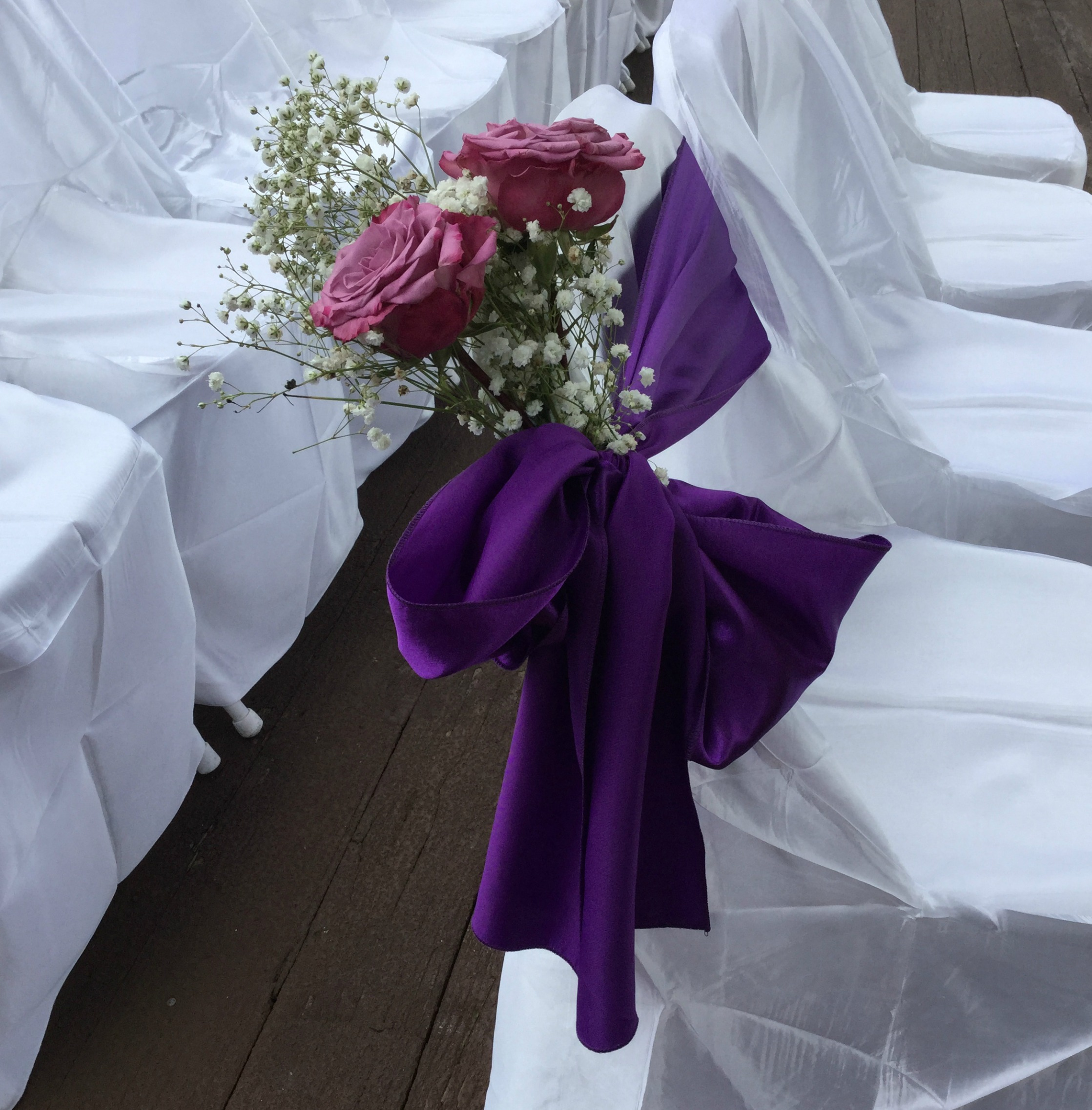 Pink flowers with purple ribbon and bow at outdoor wedding at Ivy Hall in GA