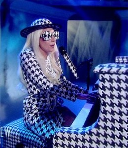 Lady Gaga playing piano black and white outfit with glasses and hat