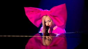 Lady gaga playing the piano in outfit huge pink bow in hair